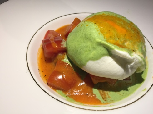 Burrata on a bed of cherry tomatoes in its juice dressed in a light pesto ruccola sauce